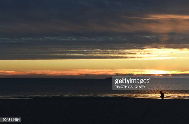 A man walks along the surf in the very cold air as the sun comes up on the beach at Tod's Point Beach in Old Greenwich Connecticut on January 14 2018...