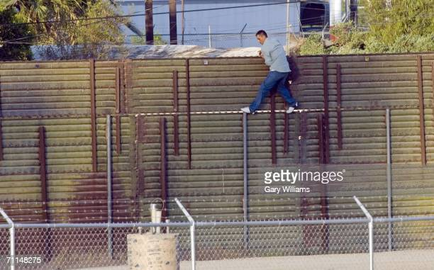 A man walks along the US side of the 15foot high border fence toward a Border Patrol agent in a truck after scaling the barrier from Mexico June 7...