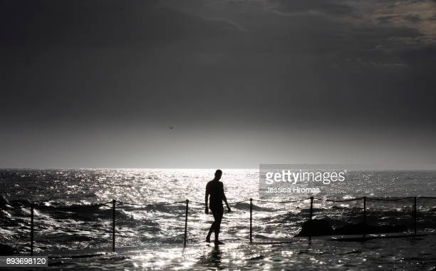 A man walks along the wall of the ocean pool at Bronte Beach on another hot and steamy morning on December 16 2017 in Sydney Australia Sydney has...
