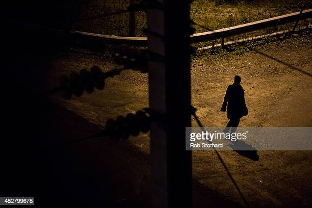 A man walks along train tracks near the Eurotunnel terminal in Coquelles on August 3 2015 in Calais France Hundreds of migrants are continuing to...