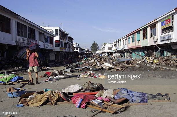 A man walks amid dead bodies and debris thrown around by a Tsunami that hit the Indonesian City of Banda Aceh 150 miles from southern Asia's massive...