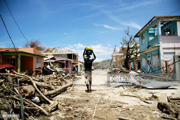A man walks amid destruction on a street September 23 2017 in Roseau on the Caribbean island of Dominica following passage of Hurricane Maria...