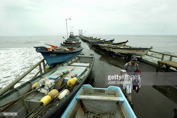 A man walks amid fishing boats taken out of the water and placed on the jetty of El Puerto de La Libertad 31 km from San Salvador 05 September 2007...
