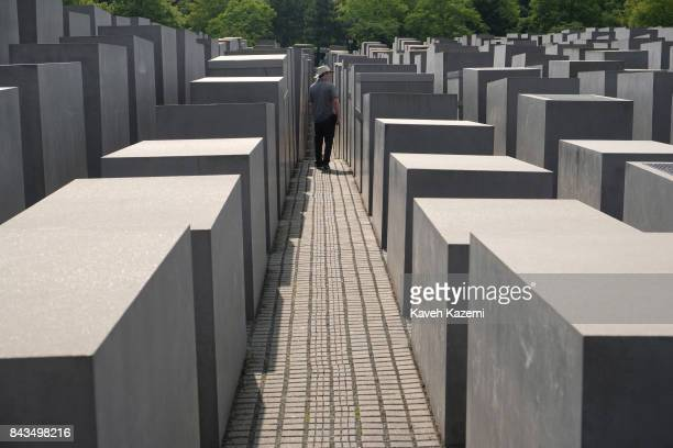 A man walks amid the concrete slabs or 'stelae' in The Memorial to the Murdered Jews of Europe also known as the Holocaust Memorial designed by...