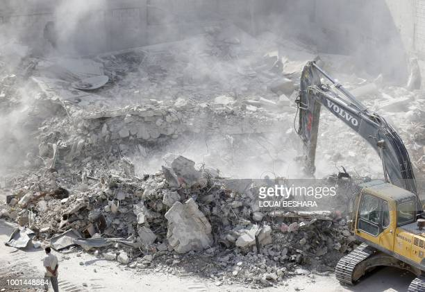 A man walks amid the rubble of destroyed buildings being removed by a bulldozer in Harasta on the outskirt of the Syrian capital Damascus on July 15...