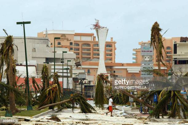 A man walks amidst the debris 23 October in the hotel area in Cancun after the city was hit by Hurricane Wilma Although heavy rains had subsided as...