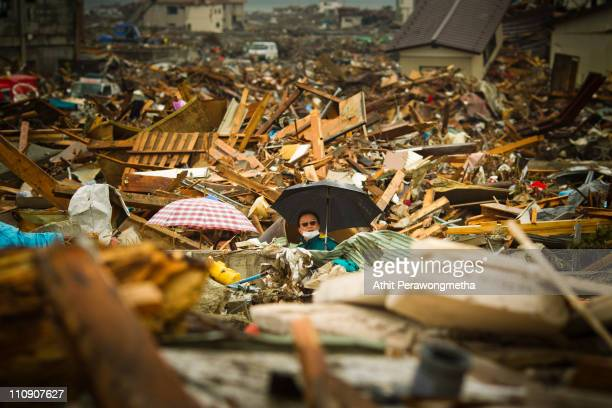 A man walks among debris at Rikuzentakata on March 26 2011 in Iwate Prefecture Japan The 90 magnitude strong earthquake struck offshore on March 11...