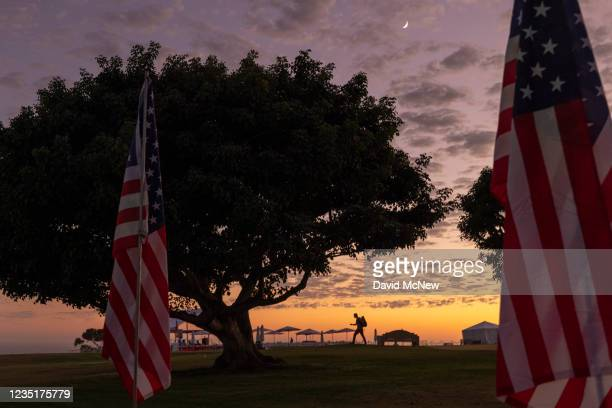 Man walks among flags during the 14th annual Waves of Flags on the eve of the 20th anniversary of the September 11 terror attacks in Alumni Park at...