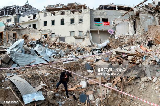 Man walks among the debris of destroyed buildings hit by shelling during the ongoing military conflict between Armenia and Azerbaijan over the...