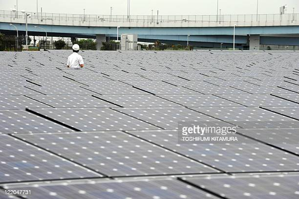 A man walks amongst solar cells at the Ukishima Solar Power Plant in Kawasaki city Kanagawa prefecture south of Tokyo on August 25 2011 Using solar...