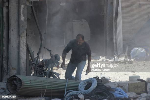 A man walks amongst the debris of apartments and buildings after airstrikes hit residential areas of Jisr alShughur in the northwestern Idlib...