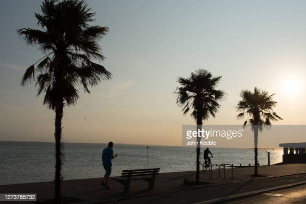 Man walks and a cyclist rides along the sea front as the sun goes down during the recent warm weather on September 20, 2020 in Southend on Sea,...