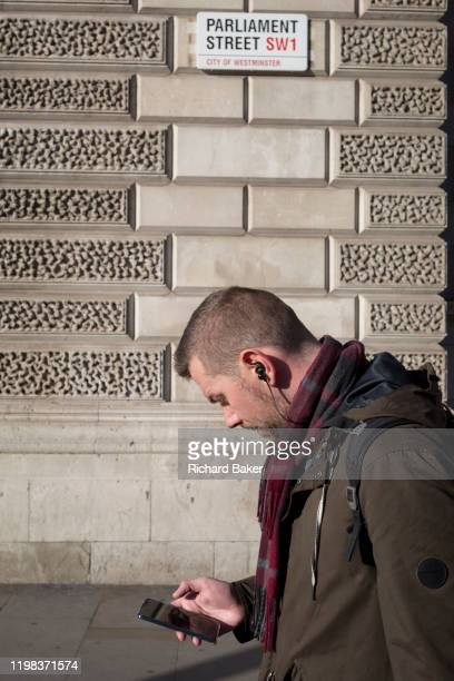 Man walks and looks at his phone beneath the signpost for Parliament Street SW1, Westminster, on 29th January 2020, in London, England.