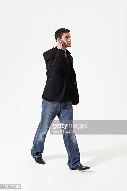 A man walks and talk on his cel phone.