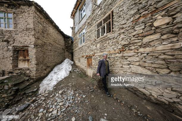 A man walks around in front of stone houses at a village at Hizan district in the southeastern province of Bitlis Turkey on February 18 2018 Most of...