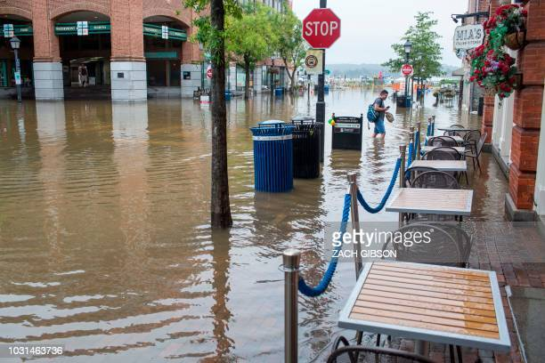 A man walks as rainwater floods outside buildings in Old Town Alexandria Virginia on September 11as sandbags were being distributed to businesses and...