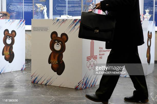 Man walks at a hall of the Russian Olympic Committee headquarters decorated with images of the 1980 Moscow Olympics mascot - Misha the bear - in...