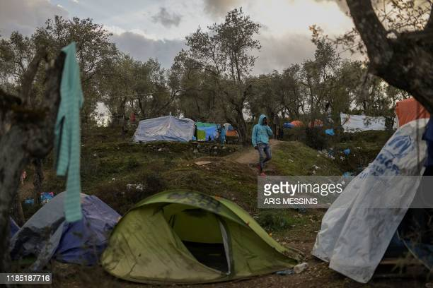 Man walks at a makeshift camp outside the overcrowded Moria camp near the capital Mytilene in the island of Lesbos on November 28, 2019. - Conditions...
