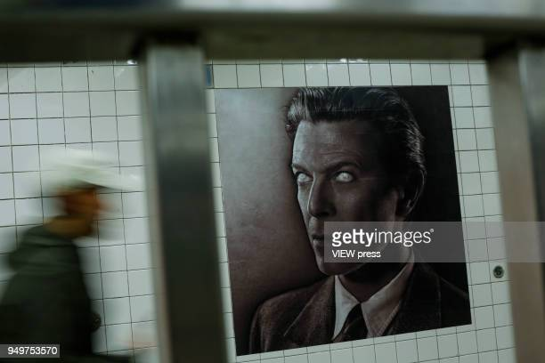 A man walks at a subway station while images of David Bowie are displayed as art installations on April 20 2018 in New York NY A Bowie exhibition...
