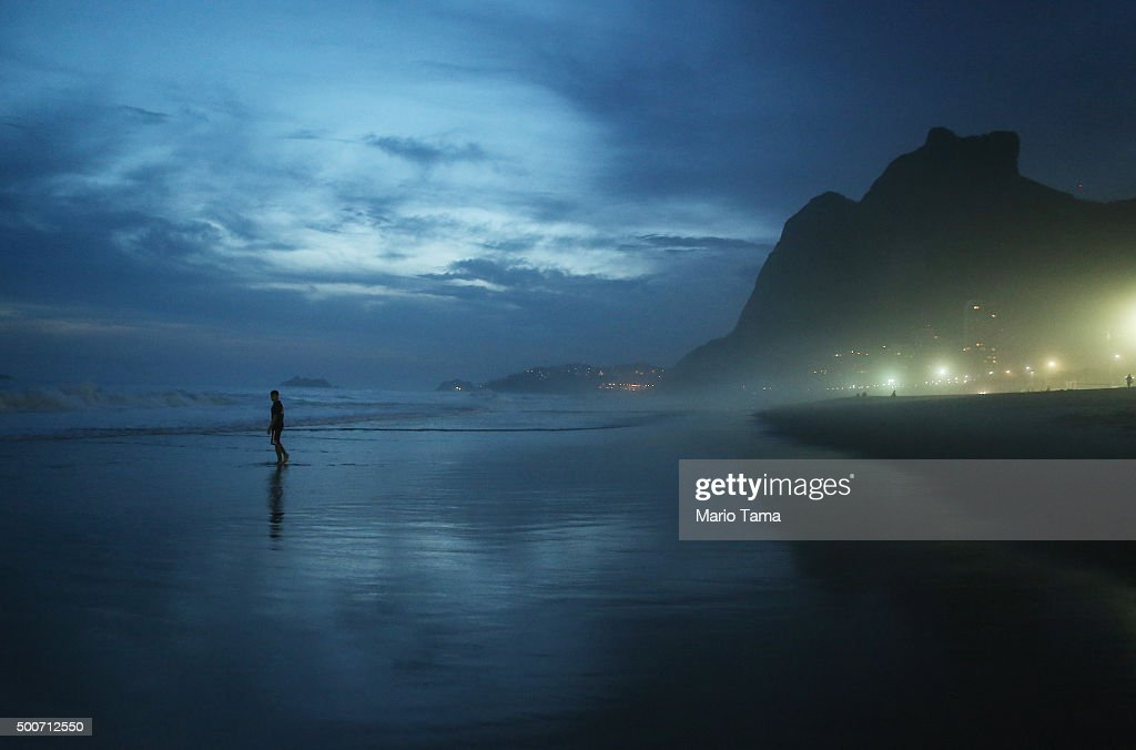 A man walks at dusk along Sao Conrado beach on December 9, 2015 in Rio de Janeiro, Brazil. The city is set to host the Rio 2016 Olympic Games next summer.