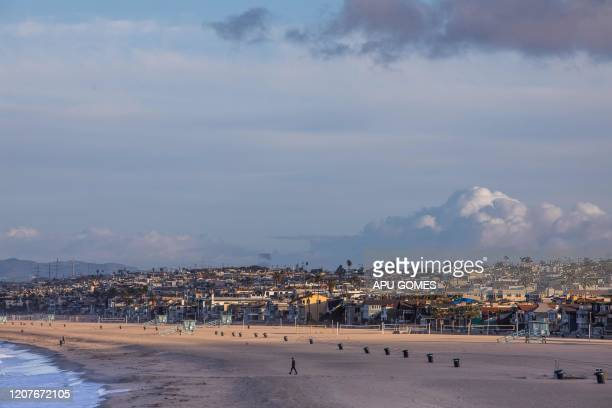 A man walks at Hermosa beach in Los Angeles California on March 19 2020 The US government is now preparing for 18 months of the coronavirus pandemic...