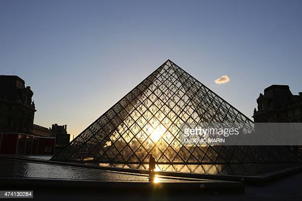 Man walks at sunset in front of the Louvre Pyramide on May 20, 2015 in Paris. AFP PHOTO / LUDOVIC MARIN