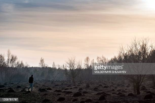 A man walks at the scene of a forest fire at a 30kilometer Chernobyl exclusion zone in Ukraine not far from the nuclear power plant on April 12 2020...