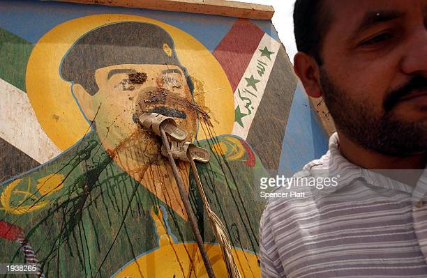 A man walks away from a mural of Saddam Hussein after smearing it with mud and placing shoes on the face a severe insult in the Muslim religion on...