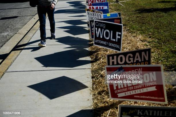 TOPSHOT A man walks away past campaign signs after voting during early voting at a community center October 25 2018 in Potomac Maryland two weeks...
