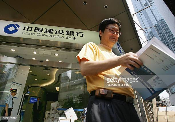 A man walks away with a prospectus for the Initial Public Offering of China Construction Bank in Hong Kong 14 October 2005 The CCB is the Fourth...