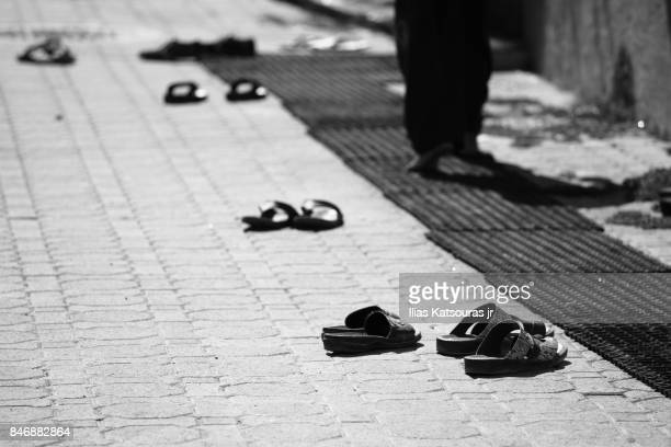 Man walks barefoot after leaving shoes outside mosque in Al Seeb, Muscat, Oman