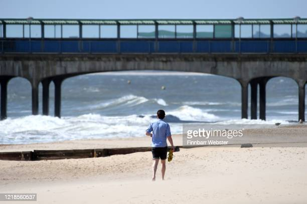 Man walks barefoot at Boscombe beach on April 13, 2020 in Bournemouth, United Kingdom. The Coronavirus pandemic has spread to many countries across...