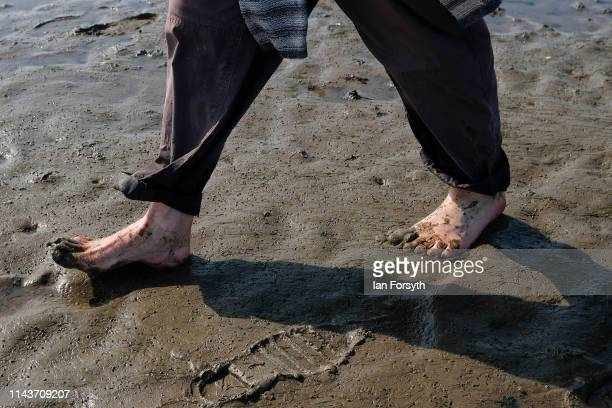 Man walks barefoot through the mud as he joins Pilgrims celebrate Easter by carrying wooden crosses as they walk over the tidal causeway to...