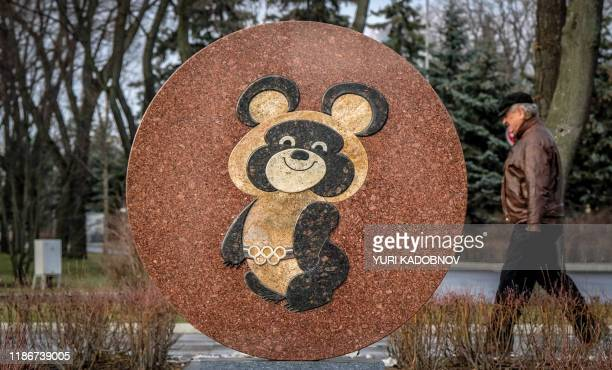 Man walks behind a monument to the mascot for the 1980 Moscow Olympics - Misha the bear - near the Luzhniki stadium in Moscow on December 6, 2019. -...