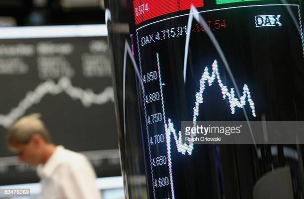 A man walks behind an index board showing the German DAX Index during a trading session on the floor of Frankfurt stock exchange on October 29 2008...