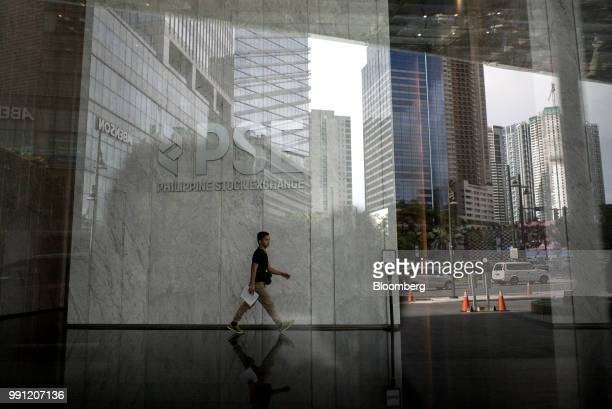 A man walks below signage for Philippine Stock Exchange Inc displayed in the lobby of the bourse in Bonifacio Global City Metro Manila the...