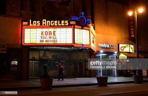 """Man walks below the marquee of the Los Angeles Theater reading """"Kobe you will be missed"""" as people mourn the death of NBA legend Kobe Bryant, who was..."""
