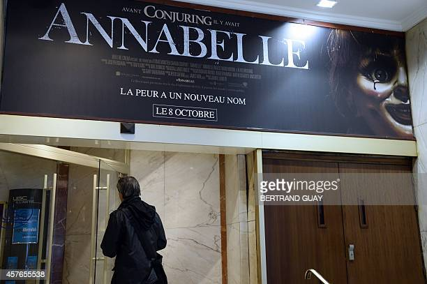 A man walks beneath a poster of the horror film ''Annabelle'' as he enters a movie theater on October 22 2014 in Paris Several cinemas across France...