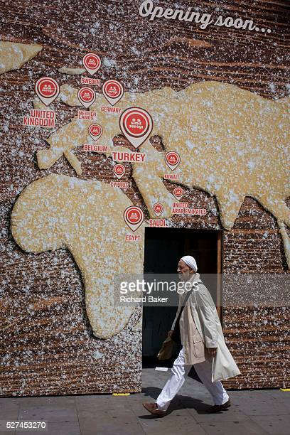 Man walks beneath a world map on a bakery business hoarding The male passes beneath the large billboard screening off construction work for a new...