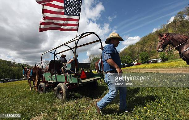 A man walks beneath an American flag at the Owsley County Saddle Club trail ride on April 20 2012 in Booneville Kentucky The trail ride attracts...