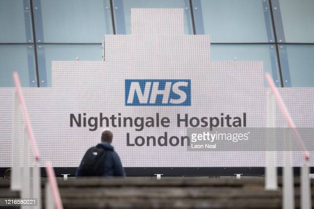 A man walks beneath the signage at the main entrance ahead of the official opening of the NHS Nightingale Hospital at ExCel on April 3 2020 in London...