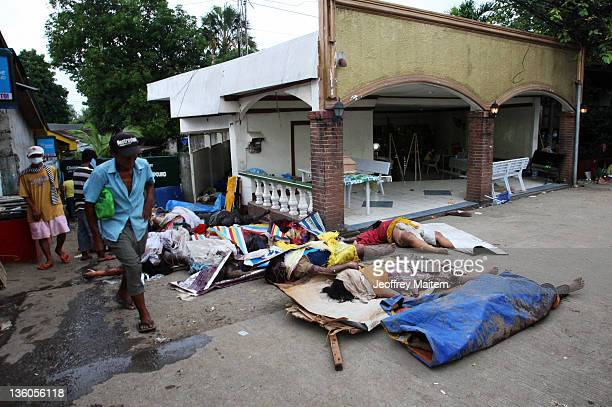 A man walks beside dead bodies of storm victims on December 18 2011 outside the funeral parlor in Cagayan de Oro Philippines Typhoon Washi a tropical...