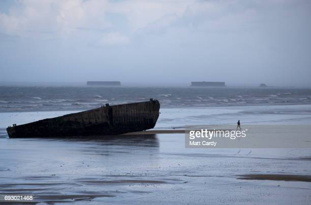 A man walks besides the remains of the Mulberry Harbour on the beach at Arromanches as commemorations to mark the 73rd anniversary of the DDay...