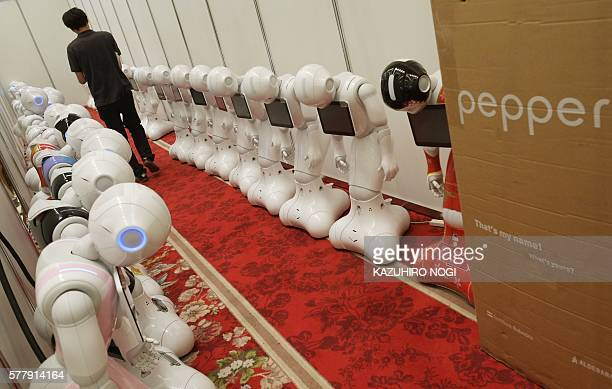 A man walks between Japan's telecom giant Softbank's 'Pepper' humanoid robots in a hotel in Tokyo on July 20 ahead of the exhibition Pepper World...