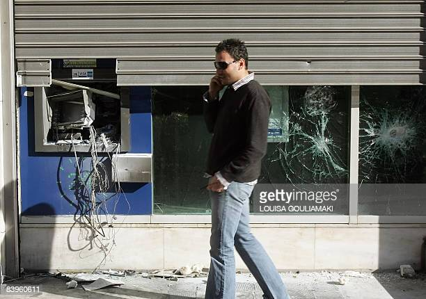 A man walks by a bank destroyed during overnight riots in Athens on December 9 2008 Authorities closed off many Athens streets Tuesday after a third...
