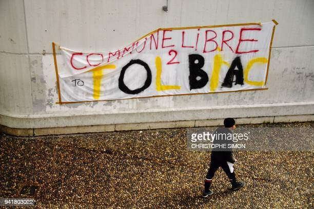 A man walks by a banner reading in French 'Free town of Tolbiac' in a courtyard of the Paris 1 Pantheon Sorbonne University's Tolbiac site on Avril 4...