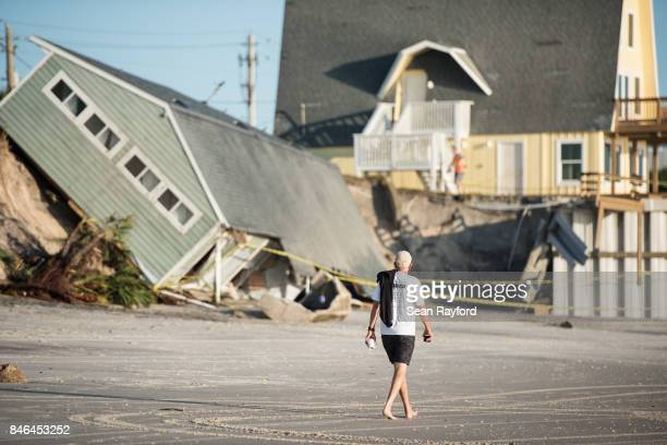 A man walks by a beachfront home destroyed by Hurricane Irma on September 13 2017 in Vilano Beach Florida Nearly 4 million people remained without...