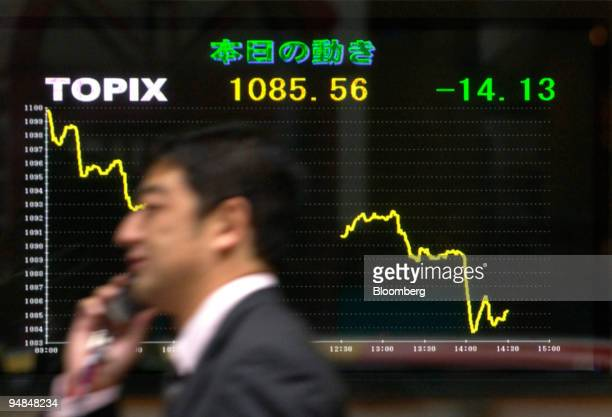 A man walks by a board displaying the TOPIX movement for the day on Thursday December 9 2004 in Tokyo Japan Asian stocks fell led by...