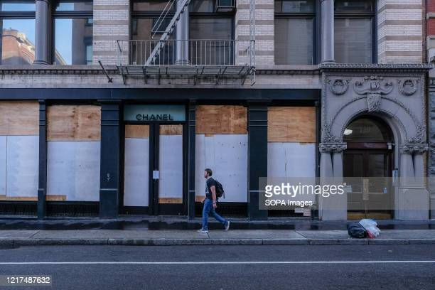 A man walks by a boarded up Chanel store in SOHO in lowerManhattan on the morning after the eighth day of George Floyd protests in New York City