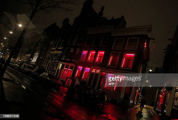 Man walks by a building with red light windows where prostitutes work in the streets of Amsterdam on December 21, 2012. AFP PHOTO / ALEXANDER KLEIN